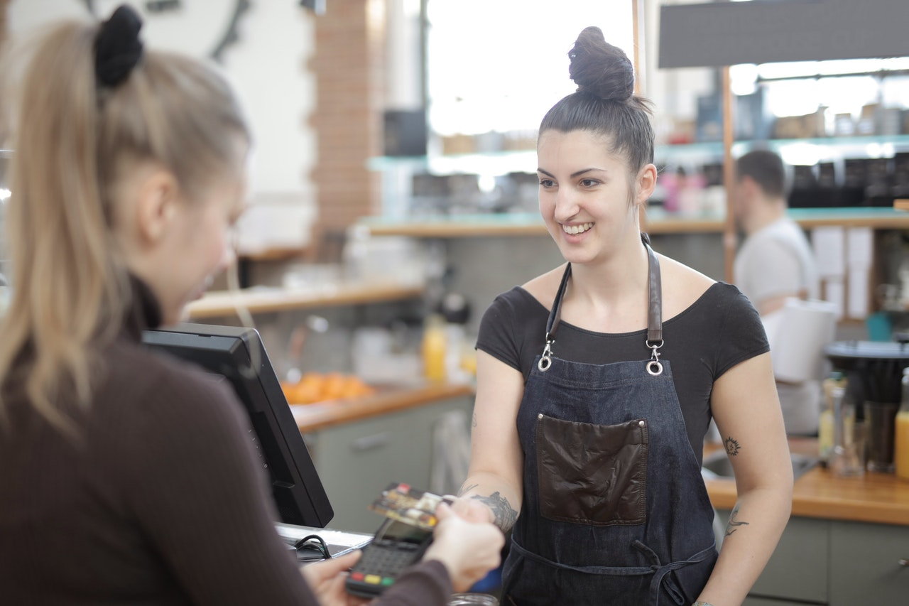 Woman showing customer satisfaction at the retail counter